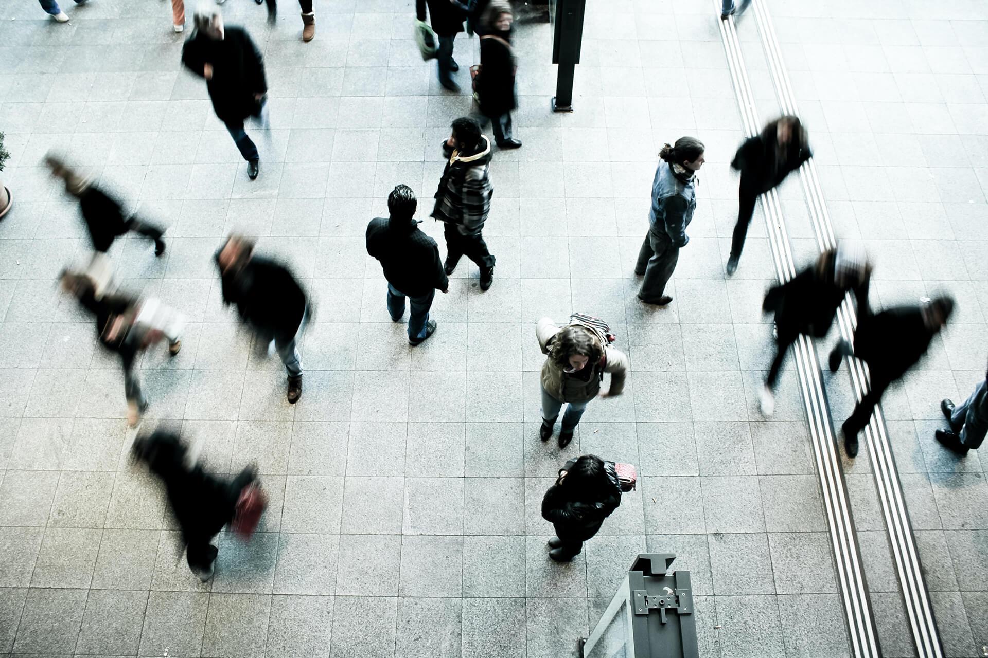 Menschen laufen auf einem Platz herum