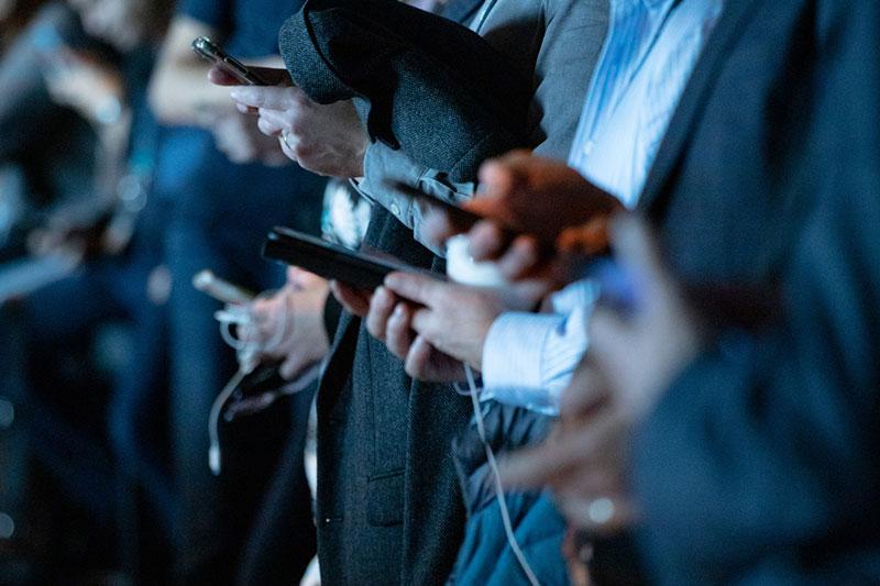 Hände mehrerer Personen, die Smartphones halten